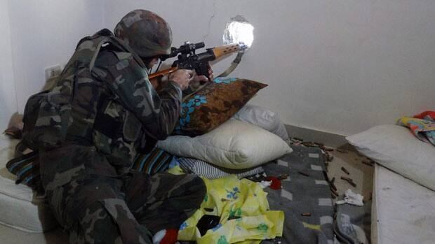 In this Sunday, Dec. 2, 2012 photo, released by the Syrian official news agency SANA, a Syrian soldier aims his rifle at free Syrian Army fighters during clashes in the Damascus suburb of Daraya, Syria.