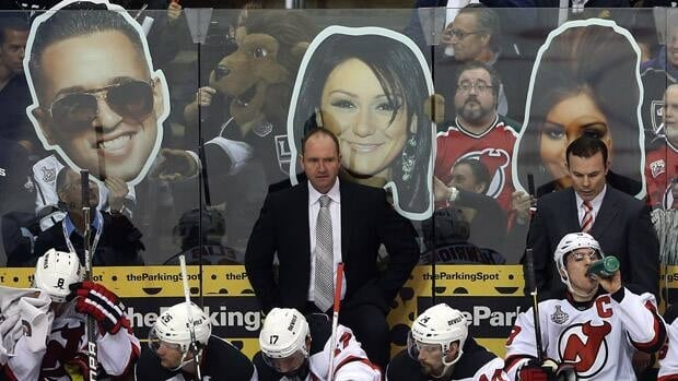Head Coach Peter DeBoer, centre and Assistant Coach Adam Oates, right, of the New Jersey Devils look on from the bench area in front of cardboard cut-outs of the cast members of Jersey Shore in the first period of Game 3 on Monday in Los Angeles.