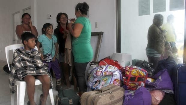Residents arrive at a shelter in Mahahual, Mexico on Tuesday ahead of the arrival of Ernesto, which hit the region as a hurricane.