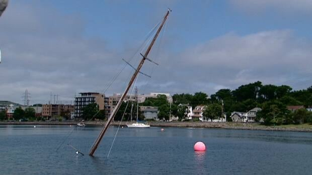 Just the mast of the vintage boat juts out of the Water near the Armdale Rotary
