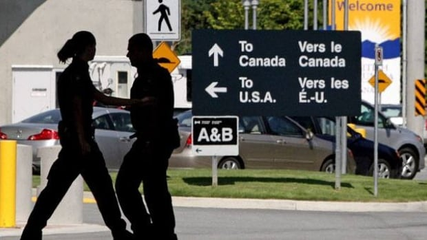 Canadian border guards at the Douglas crossing in Surrey, B.C., in 2009. More than 1,000 jobs are slated for elimination at the Canada Border Services Agency.