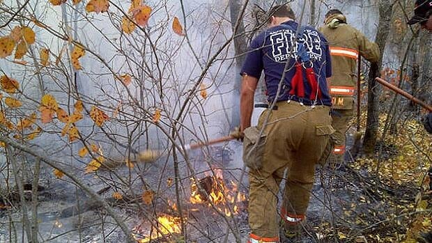 Firefighters pound at flames in Assiniboine Forest with brooms on Wednesday.