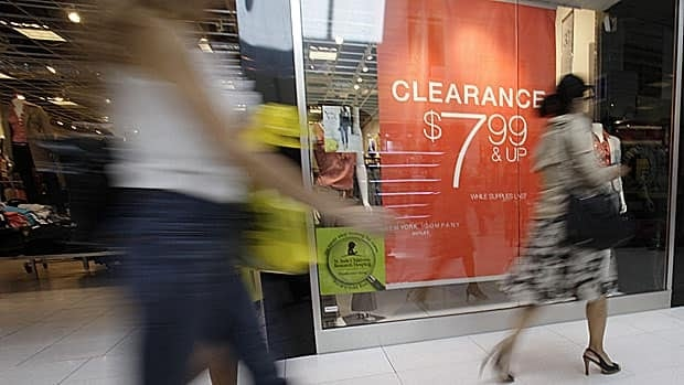 Shoppers walk past a book clearance sign at a store in Miami in November. Canadians are angry about the higher cost of books in Canada, a Senate national finance committee was told Tuesday.