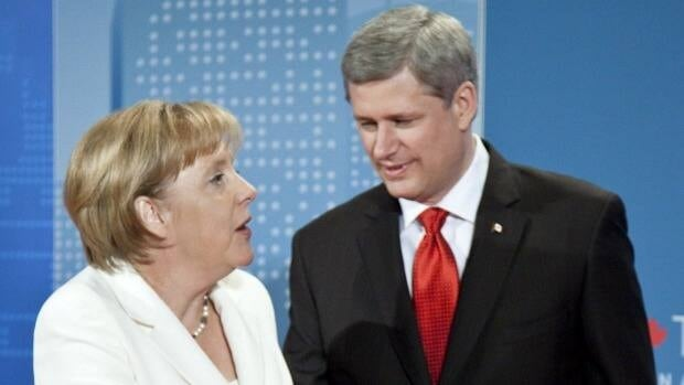 Prime Minister Stephen Harper greets German Chancelor Angela Merkel during a official dinner at the G20 Summit Saturday, June 26, 2010 in Toronto.