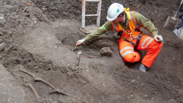 In this image posted on the Crossrail websites, workers examine skeletons found during a railway dig.