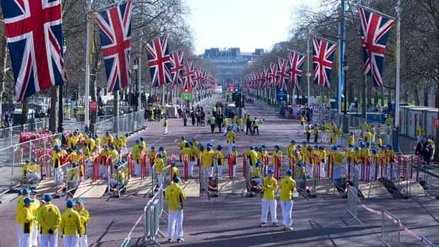 Volunteers in bright yellow get ready prior to the London Marathon in the Mall.