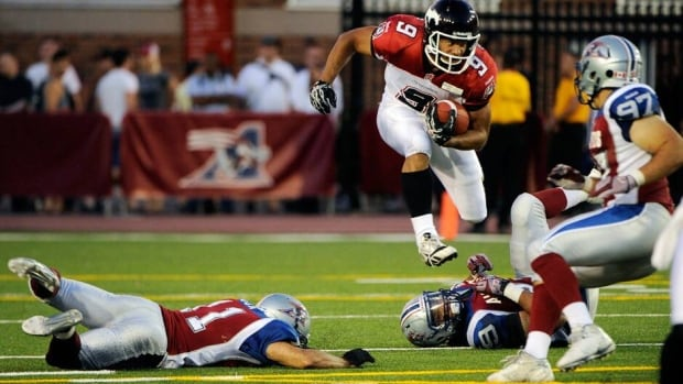 Jon Cornish (9) of the Calgary Stampeders jumps to avoid a tackle by Chip Cox (11) of the Montreal Alouettes on Friday.