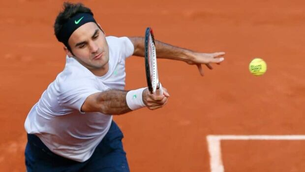 Switzerland's Roger Federer hits a return to France's Gilles Simon, not pictured, during their French Open round match Sunday at Roland Garros.