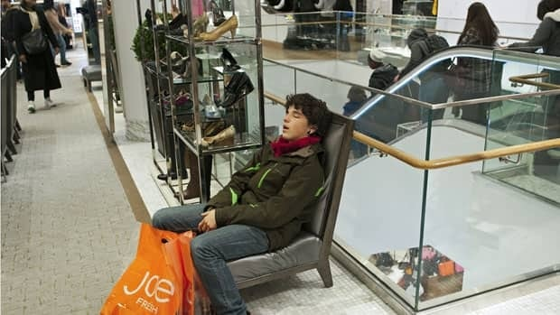 A shopper sleeps at Macy's Manhattan store on Dec. 24. Retailers can often make as much as 40 per cent of their annual revenue during the final two months of the year.