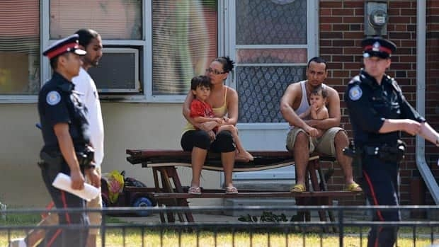 Neighbours watch on as police walk by on July 17, 2012 near the scene of a shooting the previous night on Danzig Street where 23 people were wounded by gunfire and 2 died.