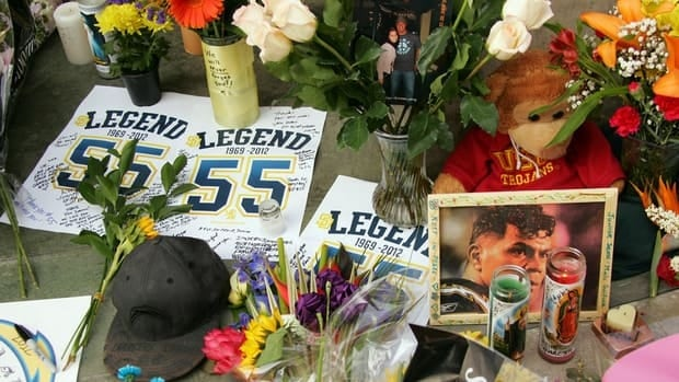 A memorial for NFL legend Junior Seau builds as fans show their respect to the recently deceased football star at the entrance way of Seau's Restaurant in Mission Valley on Thursday.