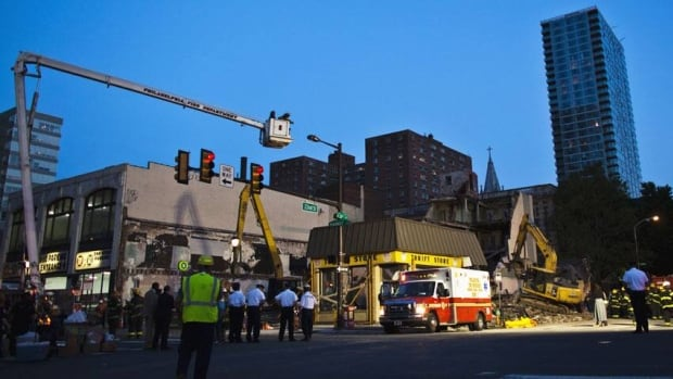 Firefighters and rescue workers search through rubble following a building collapse in Philadelphia on June 5, 2013.