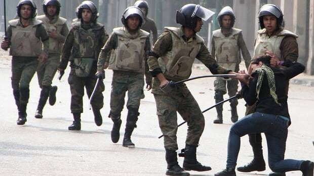 Egyptian army soldiers arrest a woman during clashes with military police near Cairo's downtown Tahrir Square in December 2011.