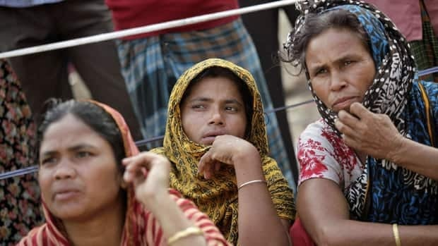 Locals watch the rescue operation at the collapsed garment building in Bangladesh. The building housed factories that made low-cost garments for Western brands such as Joe Fresh.