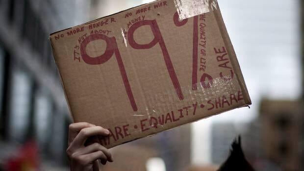 A protestor holds up a sign near Toronto's financial district on Saturday. Data from Statistics Canada shows that the recession actually slowed the income gap between rich and poor.