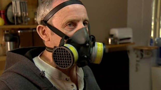 Mike Labrecque wears a gas mask when he visits his Peace Country property, which he moved from two years ago.