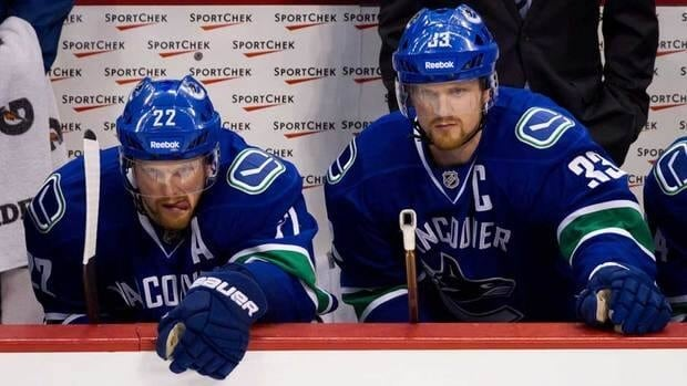 Vancouver Canucks' Daniel Sedin, left, was injured March 21 when he took an elbow to the head, but brother Henrik, right, says he is improving.