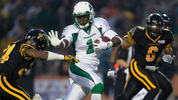 Saskatchewan Roughriders running back Kory Sheets tries to avoid a hit by Hamilton Tiger-Cats' Arthur Hobbs during the second quarter.