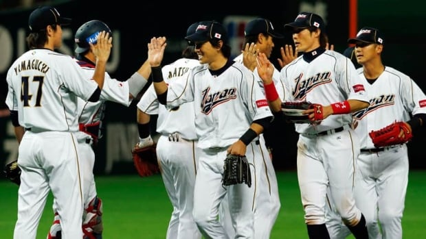 Japanese players from right, Sho Nakata, Yoshio Itoi, Hisayoshi Chono, centre, and other players celebrate after defeating China in the World Baseball Classic first round game in Fukuoka, Japan on Sunday.