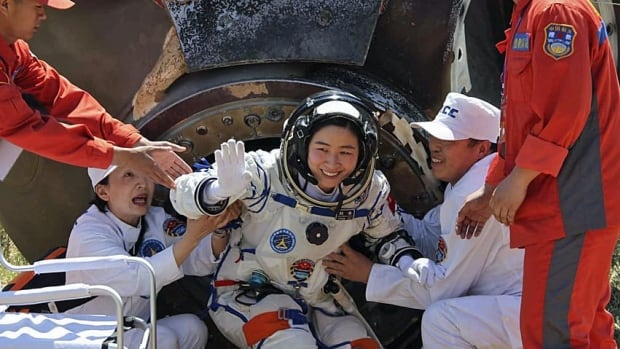 China's first female astronaut Liu Yang waves as she comes out of the re-entry capsule of the Shenzhou-9 spacecraft in Siziwang Banner of north China's Inner Mongolia Autonomous Region on Friday.