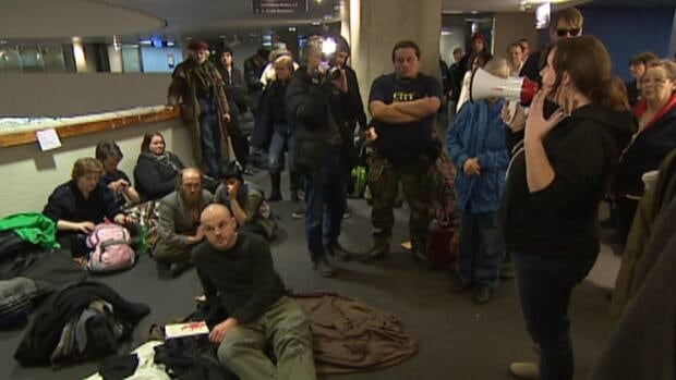 Protesters trying to raise awareness about Toronto's lack of shelter beds for the homeless were escorted out of city hall Friday night.