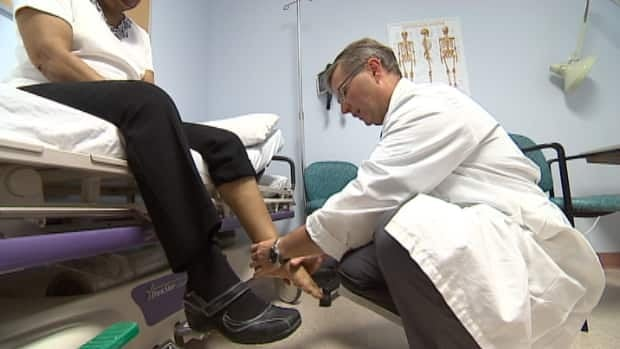 Dr. Mark Glazebrook, who's about to become Nova Scotia's only foot and ankle surgeon, examines Myra Bailey. She waited eight years to see a specialist.