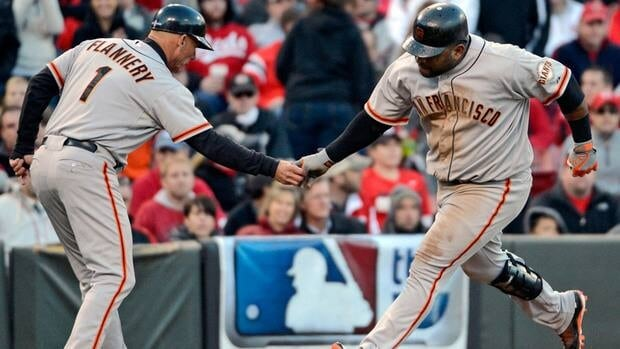 San Francisco Giants' Pablo Sandoval is congratulated by third base coach Tim Flannery after hitting a two-run home run against the Cincinnati Reds in the seventh inning of Game 4 Wednesday.