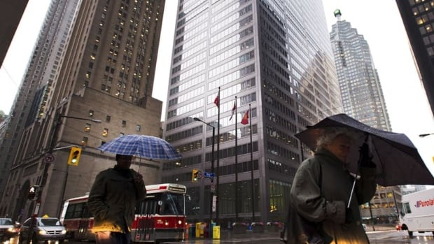People take cover under umbrellas in Toronto's financial district as weather worsens in Toronto on Monday. Hurricane Sandy is affecting the U.S. East Coast and is expected to reach southern Ontario later in the evening.