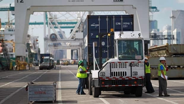 Workers handle shipping containers at the Port of Miami. The U.S. trade deficit widened in December to $48.8 billion US.