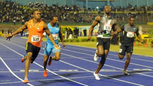 Yohan Blake, left, celebrates after crossing the finish line ahead of current world-record holder Usain Bolt, second from right, to win the 100m final at Jamaica's Olympic trials in Kingston, on Friday, Blake also beat Bolt in the 200-metre final on Sunday.