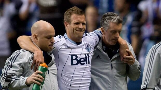 Vancouver Whitecaps captain Jay DeMerit is carried off the field after being injured during the first half of the season opener on Saturday.