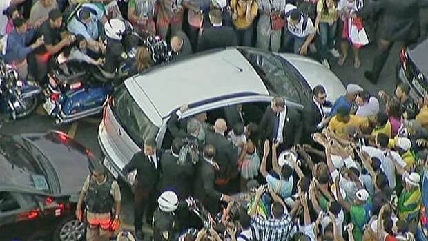 The car carrying Pope Francis is mobbed by well-wishers as it gets stuck in traffic as he is driven from the airport to the Metropolitan Cathedral in downtown Rio de Janeiro on Monday. The still image is taken from a video.