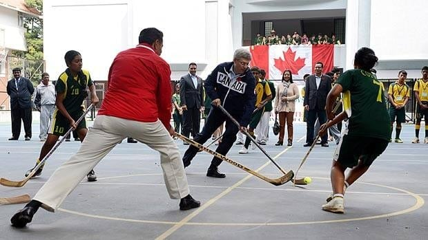Prime Minister Stephen Harper and Amateur Sport Minister Bal Gosal play ball hockey with students at the Bishop Cotton Boys and Girls School in Bangalore, India on Friday.