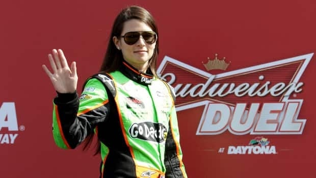 Danica Patrick waves to the crowd prior to the NASCAR Sprint Cup Series Budweiser Duel 1 at Daytona International Speedway on February 21, 2013.