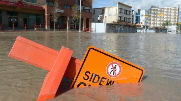 A sidewalk sign sits almost completely under water on flooded streets of Calgary on Friday.
