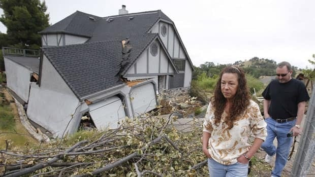Robin and Scott Spivey walk past the wreckage of their Tudor-style dream home they had to abandon when the ground gave way causing it to drop three metres below the street in Lakeport, Calif.