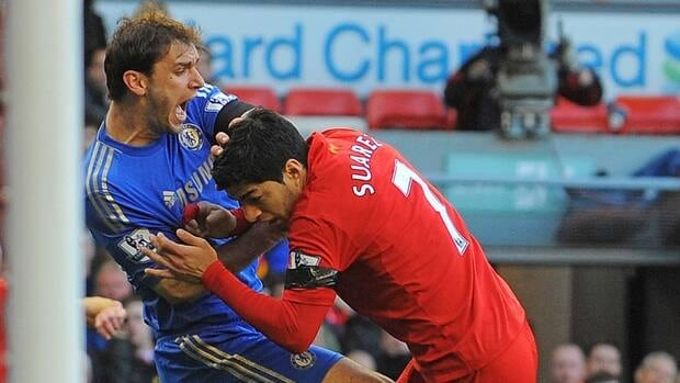 Liverpool's Luis Suarez, right, clashes with Chelsea's defender Branislav Ivanovic after appearing to bite the Chelsea player.