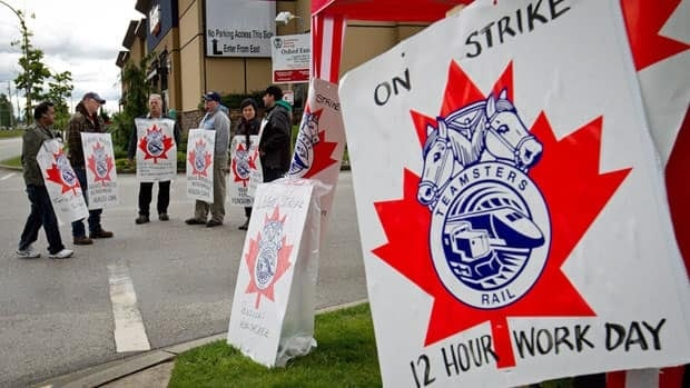Striking Canadian Pacific Railway workers picket outside the company's Port Coquitlam yard east of Vancouver on Wednesday.
