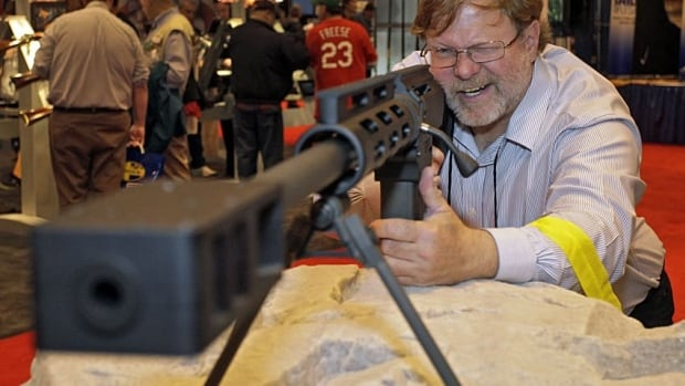 A man peers down the barrel of a Bushmaster .50-calibre rifle at a National Rifle Association show in St. Louis this year. Cerberus is selling its stake in the company that makes these guns.