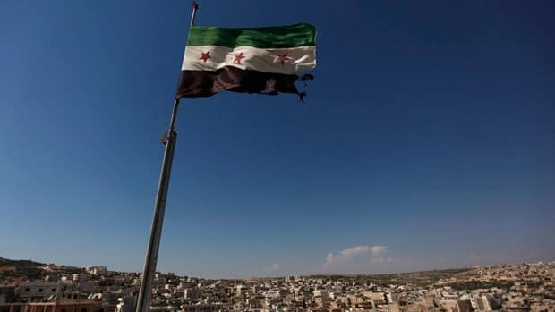 A Syrian revolutionary flag flies above buildings on the outskirts of Aleppo.