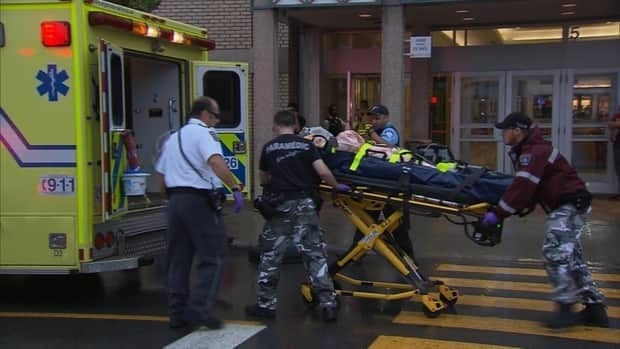 A victim is seen being brought to an ambulance after a shooting at Montreal's Galeries d'Anjou.
