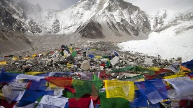 Buddhist prayer flags flutter in the wind in front of the Everest base camp. Nepalese officials are implementing new safety rules to try and minimize deaths.