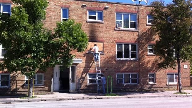 Workers board up a window at a Ellice Avenue apartment building where a fire broke up overnight Sunday.