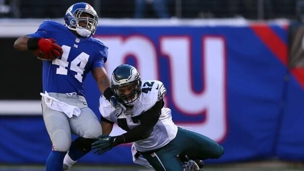 Ahmad Bradshaw, left, of the New York Giants carries the ball as Kurt Coleman, right, of the Philadelphia Eagles defends at MetLife Stadium on December 30, 2012 in East Rutherford, New Jersey.