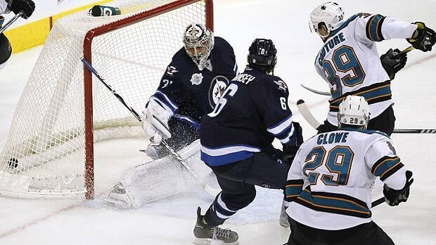 San Jose Sharks' Logan Couture scores against Winnipeg Jets goaltender Ondrej Pavelec in the second period on Thursday.
