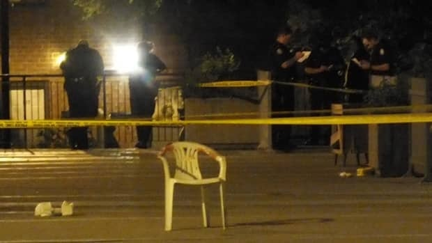 A blood-covered chair sits empty as police search for evidence at the townhouse complex.