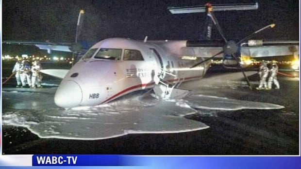 Emergency personnel spray foam on the fuselage of a US Airways Express commuter plane after it made a belly landing at Newark Liberty International Airport on Saturday. There were no injuries.