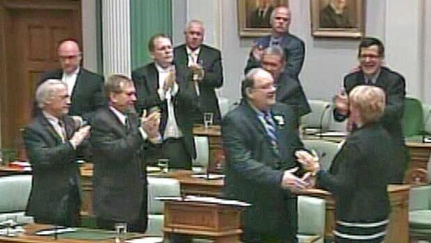 Finance Minister Tom Marshall is applauded by Tory MHAs as he shakes Premier Kathy Dunderdale's hand at the conclusion of Tuesday's provincial budget speech.