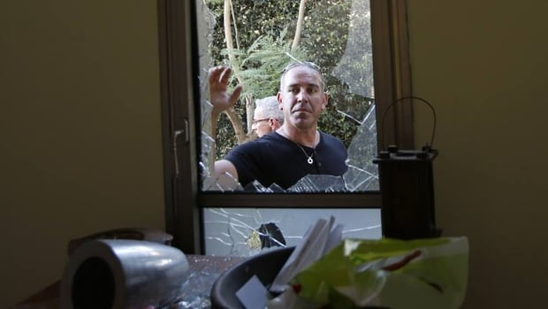 Israeli men survey a house damaged by a rocket fired from Lebanon into Israel on Thursday. Israel launched an airstrike near Beirut Friday.