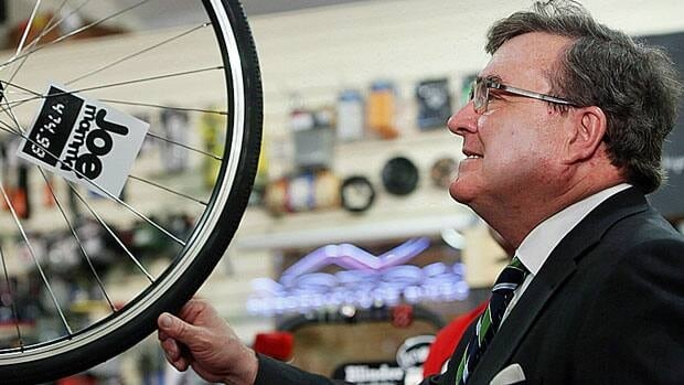 Finance Minister Jim Flaherty takes time out to look over a bicycle after a news conference at Joe Mamma's bicycle shop in Ottawa last October. The owner of the shop where Flaherty last year trumpeted the benefits of his budget, says he feels misled.